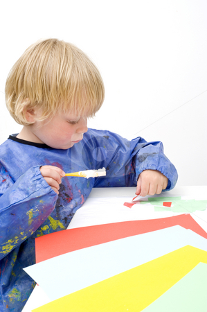 Cutting and pasting stock photo, Young child cutting and pasting pieces of colorful paper by Corepics VOF