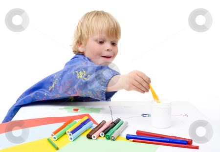 Reaching for the glue stock photo, Young boy reaching for the jar with glue across the table by Corepics VOF