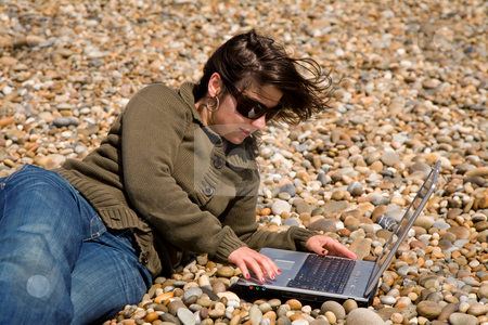 Working stock photo, Young woman at the beach working with laptop by Rui Vale de Sousa