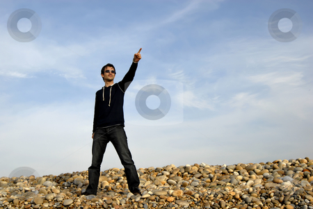 Pointing stock photo, Young man alone pointing at the beach by Rui Vale de Sousa