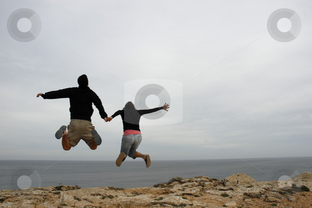 Jump stock photo, Couple jump together holding hands at the coast by Rui Vale de Sousa