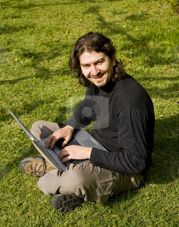 Working stock photo, Young man working with laptop at the grass by Rui Vale de Sousa