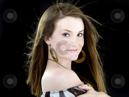 Young woman with bare shoulder against black background stock photo, Young woman with hair blown by fan dark background by Jeff Cleveland