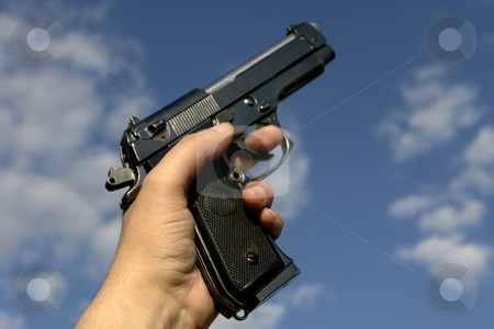 Gun stock photo, Hand withe a gun and the sky as background by Rui Vale de Sousa
