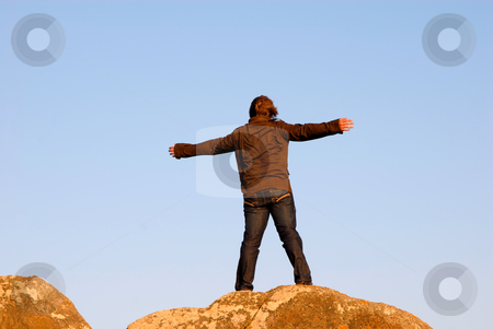 Arms wide open stock photo, Young man with arms wide open on the rocks by Rui Vale de Sousa