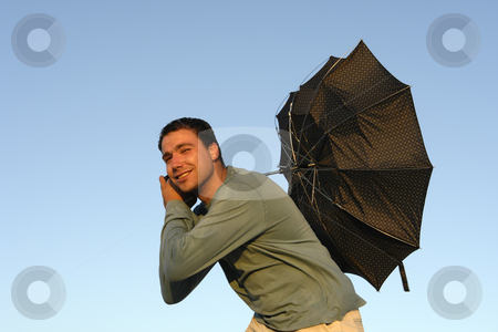 Wind stock photo, Young man with umbrella at sunset light by Rui Vale de Sousa