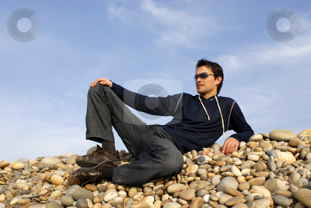 Casual stock photo, Young casual man at the beach stones by Rui Vale de Sousa