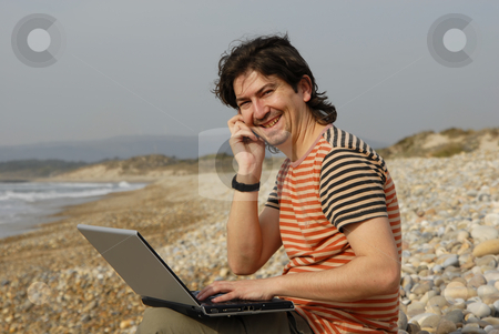 Beach stock photo, Young man at the beach with laptop by Rui Vale de Sousa