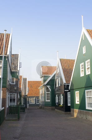 Marken stock photo, The typical style Dutch fishermans' houses on the Peninsula of Marken. The quaint wooden gables, and the archetypal green and white paint in a deserted street during a summer evening. by Corepics VOF