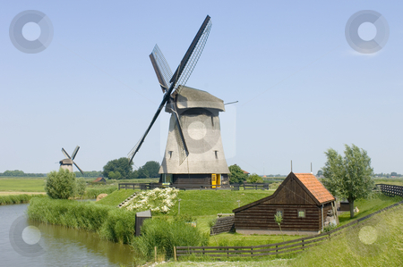 Double Dutch windmills stock photo, The archetypal image of the Netherlands; a quaint scene, with a barn, two windmills, and a lush, reed covered canal, meandring through the rural landscape by Corepics VOF