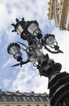 Ornamental Street light stock photo, An ornamental street light outside the Opera in Paris, with its typical cast iron lamp post and glass casings by Corepics VOF