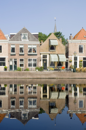 Spaarndam Reflection stock photo, The quaint village of Spaarndam, the Netherlands, with it's old, picutresque houses reflected in the water on a warm summer morning, basiking in the light by Corepics VOF