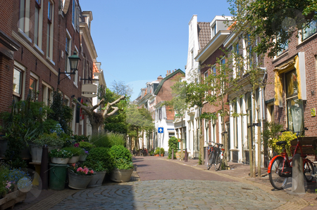 Quaint Alley stock photo, A quaint back alley in the center of Haarlem, the Netherlands, full of flowers and bicycles. As if time has come to a standstill. by Corepics VOF