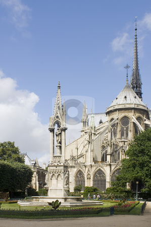 Notre Dame rear gable stock photo, The rear side of the Notre Dame Cathedral in Paris with it's beautiful and tranquil garden, just catching the sunlight. The blue sky can very well be used as copyspace by Corepics VOF