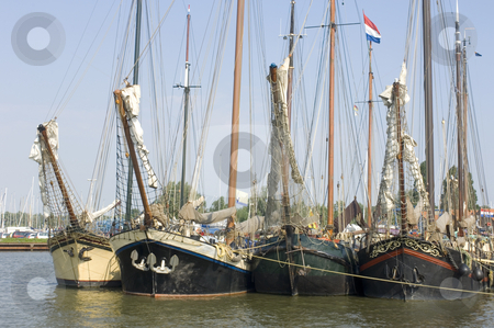 Bows in a row stock photo, A row of old sailing vessels, neatly arranged in the harbour by Corepics VOF