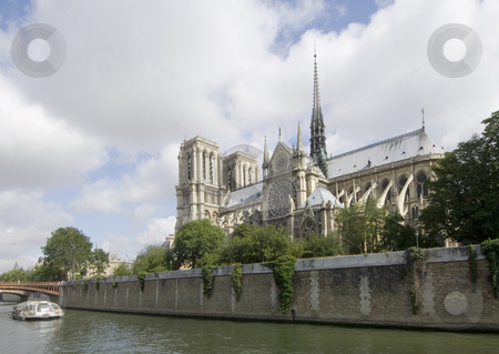 Notre Dame and the Seine stock photo, The Notre Dame in Paris, on ile de la Cit? seen from the opposite side of the river Seine. A river boat takes the tourists past all the sites; the sun strikes the roof tops of the cathedral beautifully by Corepics VOF