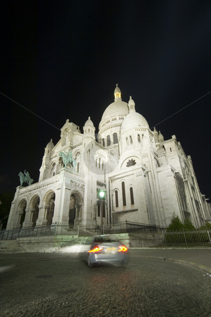 Sacr? Coeur at Night stock photo, A car turning in front of the Sacr? Coeur at night, using a wide angle perspective. The illumination of the church makes it stand out beautifully against the dark sky. by Corepics VOF