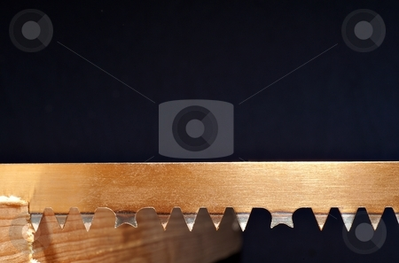 Hand saw stock photo, Detail of a blade of a hand saw in a piece of wood by Juraj Kovacik