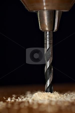 Drill bit stock photo, Detail of  drill bit in a piece of wood with dark background by Juraj Kovacik