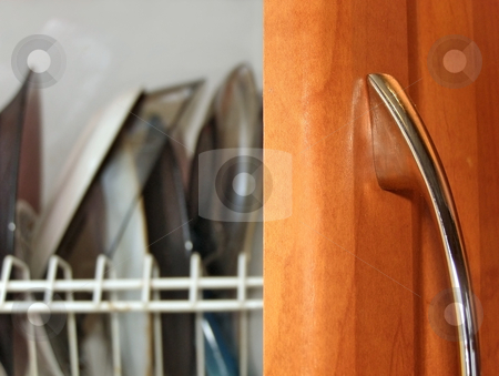 Kitchen plates stock photo, Kitchen plates over open wooden door with metallic handle by Sergej Razvodovskij