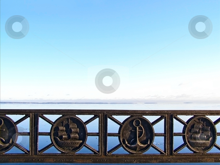 Water landscape with barrier stock photo, Tranquil water skyline with the blue sky and metal decorated barrier by Sergej Razvodovskij