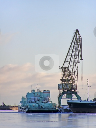 Winter port with crane stock photo, Winter cargo side port with big ships and crane by Sergej Razvodovskij