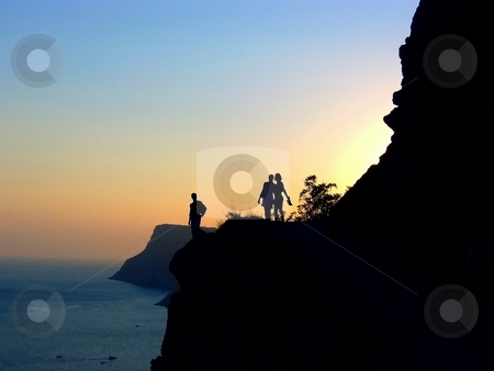 Romantic sunset stock photo, Three silhouettes on the cliff against the sunset background by Sergej Razvodovskij