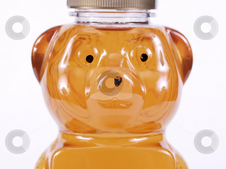 Golden Honey Bear Face stock photo, Close view of a bear shaped container full of golden honey. Over a white background. by Robert Gebbie