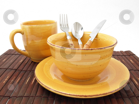 Clean Dishes stock photo, A ceramic bowl on a plate with a cup and utensils in thick earth tones atop a brown bamboo placemat. by Robert Gebbie