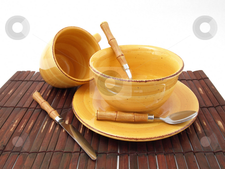 Ready for Food stock photo, A ceramic bowl on a plate with a cup and utensils in thick earth tones atop a brown bamboo placemat. by Robert Gebbie
