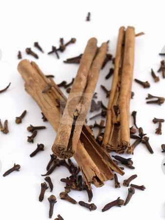 Cloves and Cinnamon stock photo, Cinnamon sticks on a spread of whole cloves. Studio isolated over white. by Robert Gebbie