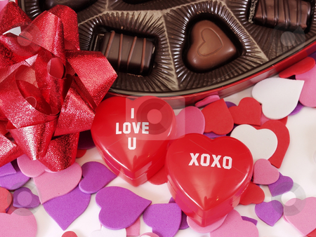 I Love U XOXO Hearts stock photo, Multi colored heart cut outs spilled around a heart shaped box of chocolate candy. A shiny red bow and 2 plastic heart boxes saying I love u and xoxo completes the setting. by Robert Gebbie