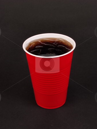 Cold Drink stock photo, A red plastic cup filled with ice and a dark beverage on a black background. With space for text. by Robert Gebbie
