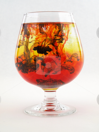 Darkness Falls stock photo, A liquid filled glass with black, red and yellow swirls over a white background. by Robert Gebbie