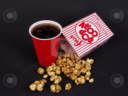 Snack Time stock photo, A spilled box of caramel corn and a red cup of soda on a black background. by Robert Gebbie