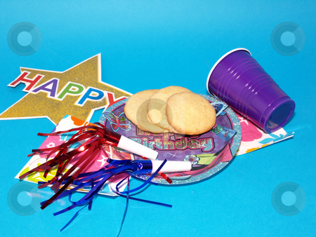 Happy Birthday Party stock photo, Colorful party supplies for a birthday party spread on a blue background. by Robert Gebbie