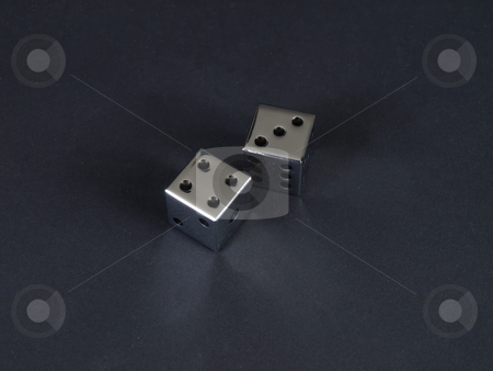 Seven Craps stock photo, Two metal dice showing a score of seven on a black background. by Robert Gebbie