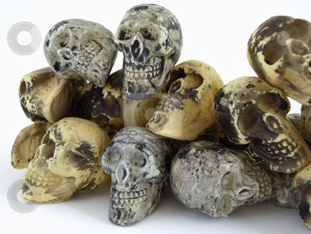 Toy Skulls in a Pile stock photo, A pile of plastic toy skulls studio isolated over a white background. by Robert Gebbie