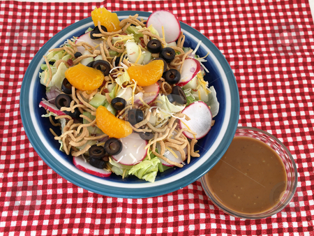 Salad and Dressing stock photo, Crisp salad of lettuce, radishes, olives, mandarin oranges, cheese and Chinese noodles. Studio isolated over a red checked cloth by Robert Gebbie