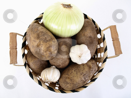 Potatoes, Onion and Garlic stock photo, A wicker basket full of baker potatoes, a large white onion, and garlic bulbs. Over a white background. by Robert Gebbie
