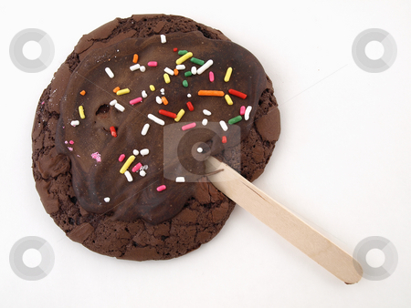 Chocolate Cookie on a Stick stock photo, A chocolate cookie with sprinkles and frosting on a stick isolated on a white background by Robert Gebbie