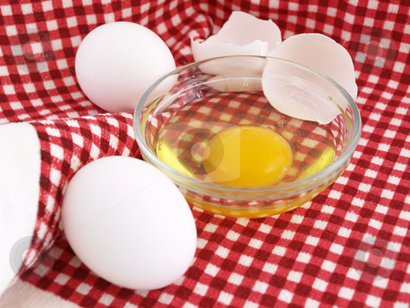 Eggs on Red Cloth stock photo, An egg cracked into a dish, eggshells and whole eggs laying on a red checkered background. by Robert Gebbie