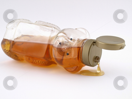 Honey Bear Drip stock photo, A plastic bear shaped container full of honey on it's side, cap open and dripping. by Robert Gebbie