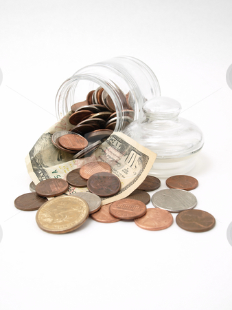 Fun Funds stock photo, A ten dollar bill cradles coins as they spill from a tipped glass jar. by Robert Gebbie