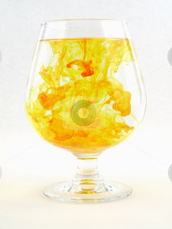 Yellow Color with Water stock photo, A liquid filled glass with yellow swirls over a white background. by Robert Gebbie