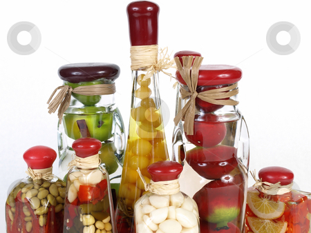 Vinegar Bottle Tops stock photo, A colorful assortment of pickled spices in different shaped jars on white. by Robert Gebbie