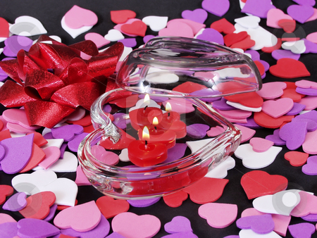 Heart Candles, Lit stock photo, Heart shaped glass dish with candles and cutouts in various colors. On black by Robert Gebbie
