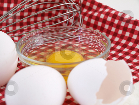 Whisk and Eggs stock photo, An egg cracked into a dish, eggshells and whole eggs with a whisk laying on a red checkered background. by Robert Gebbie