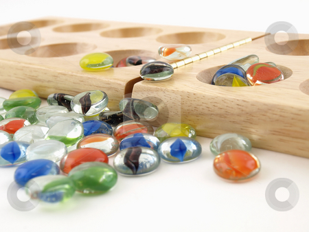 Mancala Stones and Folding Board stock photo, A folding wooden Mancala board game with glass stone pieces, isolated against a white background. by Robert Gebbie
