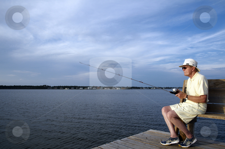 Man Fishing stock photo, A senior man fishing alone from the pier. by Darryl Vest